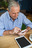 使用巧妙的电话的大角度观点的老人在桌 免版税图库摄影