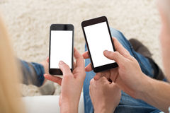 使用巧妙的电话的夫妇在家 免版税库存照片
