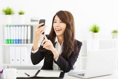 使用巧妙的电话的女商人在办公室 免版税库存照片