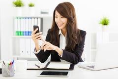 使用巧妙的电话的女商人在办公室 免版税图库摄影