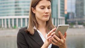 使用巧妙的电话的女实业家在街市的城市,专业女性浏览聊天的读书新闻 影视素材