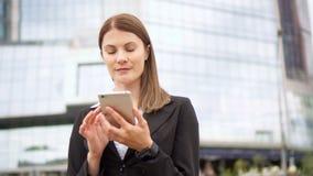 使用巧妙的电话的女实业家在街市的城市,专业女性浏览聊天的读书新闻 股票录像