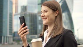 使用巧妙的电话的女实业家在街市的城市,专业女性谈的活放出 股票录像