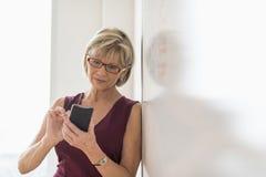 使用巧妙的电话的女实业家,当倾斜在Whiteboard时 免版税库存照片
