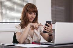 使用巧妙的电话的好女孩在工作 免版税库存照片