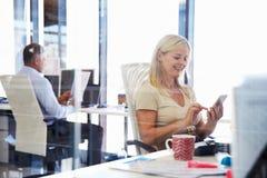 使用巧妙的电话的妇女在办公室 免版税库存图片