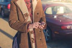 使用巧妙的电话的妇女在她的汽车旁边 库存照片