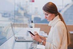 使用巧妙的电话的妇女在现代咖啡馆inerior 库存图片
