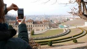 使用巧妙的电话的妇女游人,拍照片对都市全景在都灵,托里诺旅行目的地在意大利