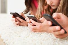 使用巧妙的电话的家庭在地毯 免版税库存图片