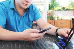 使用巧妙的电话的年轻都市专业人 拿着流动智能手机的商人使用app短信的sms消息 免版税库存照片