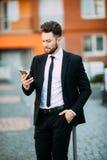使用巧妙的电话的年轻都市专业人 拿着流动智能手机的商人使用app短信的sms消息 免版税库存图片
