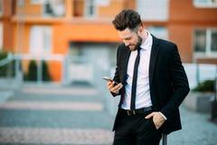 使用巧妙的电话的年轻都市专业人 拿着流动智能手机的商人使用app短信的sms消息 库存照片