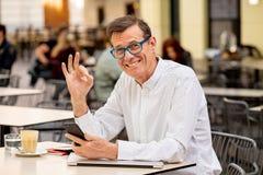使用巧妙的电话的微笑的可爱的时髦的成熟人运转网上坐在咖啡店之外 免版税图库摄影
