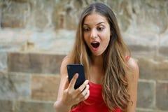 使用巧妙的电话的惊奇的少妇户外 使用新的手机的激动的都市女孩 库存图片