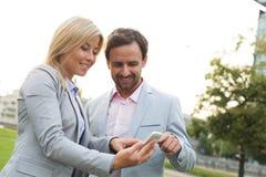 使用巧妙的电话的愉快的企业夫妇在公园 库存图片