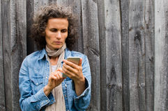 使用巧妙的电话的成熟妇女户外 免版税库存图片