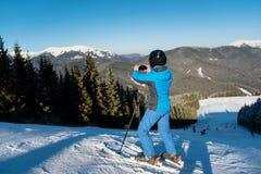 使用巧妙的电话的滑雪者在山 库存照片