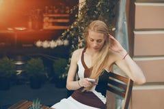 使用巧妙的电话的白肤金发的沉思美丽的妇女在咖啡馆 库存照片
