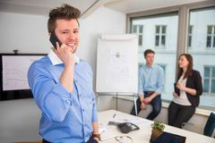 使用巧妙的电话的确信的商人在办公室 库存照片