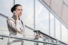 使用巧妙的电话的确信的年轻女实业家在办公室栏杆 免版税库存照片