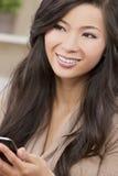 使用巧妙的电话的美丽的亚裔中国妇女 免版税库存图片