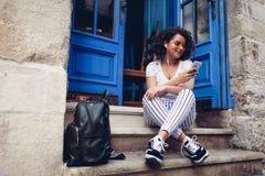 使用巧妙的电话的美丽的年轻学生女孩和听到坐由咖啡馆的音乐 库存照片