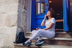 使用巧妙的电话的美丽的年轻学生女孩和听到坐由咖啡馆的音乐 库存图片