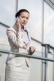 使用巧妙的电话的美丽的年轻女实业家在办公室栏杆 免版税图库摄影