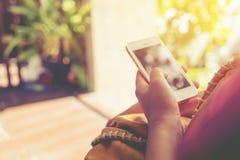 使用巧妙的电话的美丽的年轻行家妇女在咖啡店 免版税库存图片