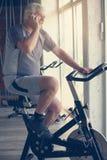 使用巧妙的电话的老人在健身房 库存图片