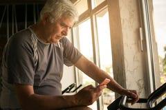 使用巧妙的电话的老人在健身房 免版税库存图片
