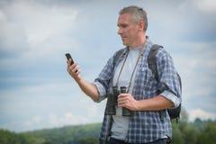 使用巧妙的电话的背包徒步旅行者 库存图片