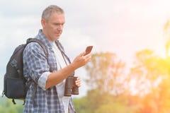 使用巧妙的电话的背包徒步旅行者 库存照片