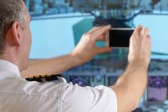 使用巧妙的电话的航空公司飞行员 库存图片