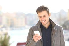 使用巧妙的电话的英俊的人在冬天 库存图片