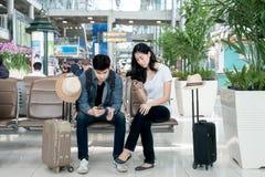 使用巧妙的电话的年轻亚洲夫妇,当坐在airpor时 图库摄影