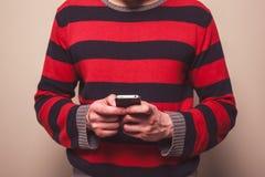 使用巧妙的电话的年轻人 免版税库存图片