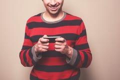 使用巧妙的电话的年轻人 库存图片