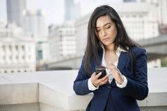 使用巧妙的电话的年轻印地安女实业家 免版税库存照片