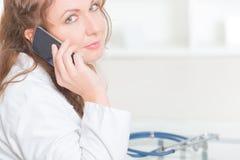 使用巧妙的电话的医师 免版税库存图片