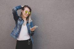 使用巧妙的电话的年轻愉快的可爱的妇女 灰色背景,复制空间 免版税库存照片