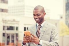 使用巧妙的电话的年轻愉快的微笑的都市专业人户外 免版税库存照片