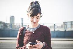 使用巧妙的电话的年轻美丽的行家妇女 免版税图库摄影