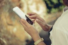 使用巧妙的电话的年轻行家妇女在街道 免版税库存图片