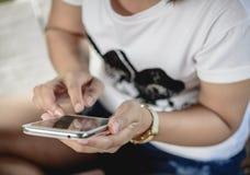 使用巧妙的电话的年轻行家妇女在街道 库存照片