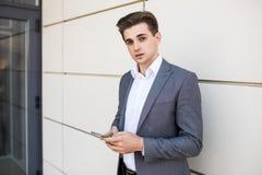 使用巧妙的电话的年轻都市专业人在办公楼户内 拿着流动智能手机的商人使用app发短信 库存图片