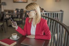 使用巧妙的电话,在咖啡店,餐馆的短信的消息的年轻白肤金发的妇女 库存图片