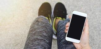 使用巧妙的电话,女性赛跑者固定的单元电话的慢跑者 图库摄影