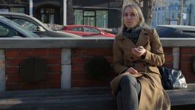 使用巧妙的电话app的美丽的妇女谈话与照相机在城市街道长凳 股票录像